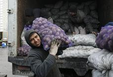 Таджикский трудовой мигрант разгружает картофель на овощном рынке под Москвой 11 ноября 2011 года. Российская рецессия резко сократила переводы трудовых мигрантов на родину из-за девальвации рубля и общего снижения заработков. REUTERS/Denis Sinyakov