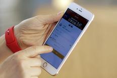 En la imagen,  un teléfono Apple usado por un empleado de la compañía en una de sus tiendas en Pekín, feb 18, 2016. Apple, que enfrenta una demanda del Gobierno de Estados Unidos para desbloquear un iPhone usado por uno de los autores del ataque en la ciudad de San Bernardino, pidió la creación de una comisión para discutir las implicancias del recurso en temas como seguridad nacional y libertades personales.  REUTERS/Damir Sagolj
