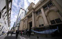 Unas personas pasando junto al Banco Central argentino en el distrito financiero en Buenos Aires, oct 2, 2014. Los acreedores enfrentados con Argentina en los tribunales de Estados Unidos por más de una década sobre bonos de deuda incumplidos llegaron a un acuerdo por 5.000 millones de dólares para resolver el conflicto, dijo el miércoles un abogado que representa a los inversores.     REUTERS/Marcos Brindicci