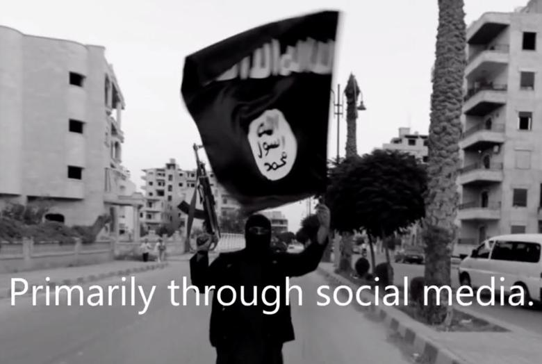A member loyal to the Islamic State in Iraq and the Levant (ISIL) waves an ISIL flag in Raqqa, Syria on June 29, 2014 in a still image taken from video produced by the student group 7Strong. REUTERS/Stringer/7Strong