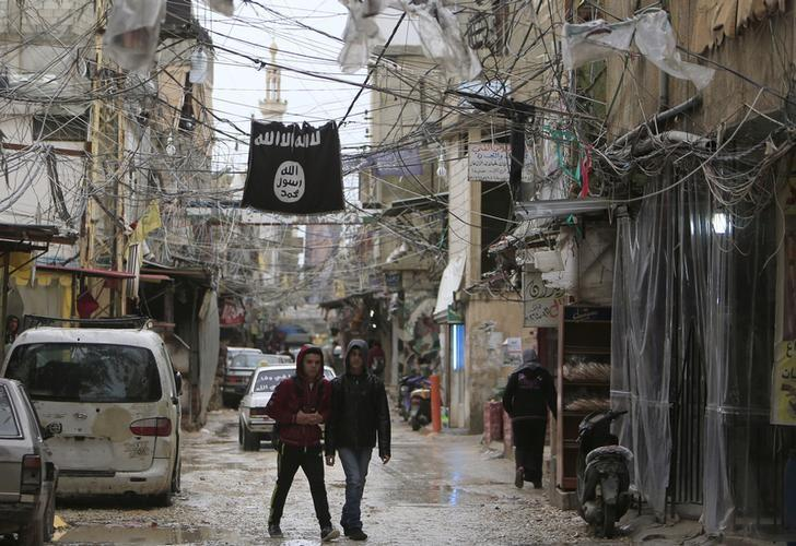 Youth walk under an Islamic State flag in Ain al-Hilweh Palestinian refugee camp, near the port-city of Sidon, southern Lebanon January 19, 2016. REUTERS/Ali Hashisho/Files
