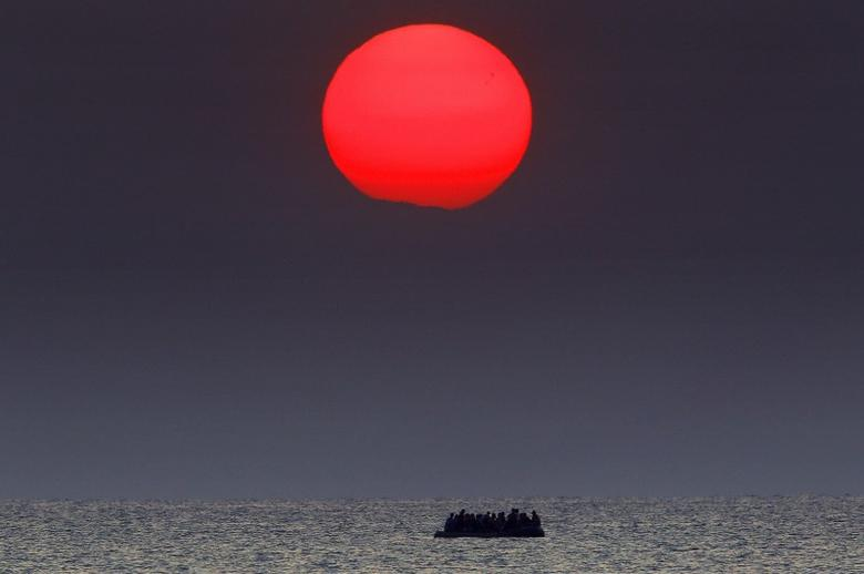 A red sun is seen over a dinghy overcrowded with Syrian refugees drifting in the Aegean sea between Turkey and Greece after its motor broke down off the Greek island of Kos, August 11, 2015. REUTERS/Yannis Behrakis