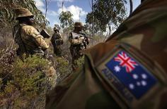 Австралийские солдаты патрулируют остров Астелл. 17 июля 2013 года. Австралия в следующие десять лет усилит расходы на оборону почти на A$30 миллиардов ($21,6 миллиарда) в попытке защитить свои стратегические и торговые интересы в Азиатско-тихоокеанском регионе на фоне борьбы США и союзников с растущей мощью Китая. REUTERS/David Gray
