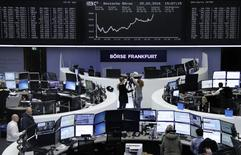 Traders work at their desks in front of the German share price index, DAX board, at the stock exchange in Frankfurt, Germany, February 25, 2016. REUTERS/Staff/Remote