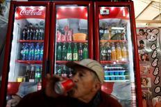 Una persona bebiendo una gaseosa en una tienda en Ciudad de México, sep 9, 2013. La mexicana Arca Continental, la segunda más grande embotelladora de Coca-Cola en América Latina, lanzó una orden de compra por aproximadamente el 25 por ciento de las acciones de inversión de Corporación Lindley que cotizan en la bolsa de Lima.  REUTERS/Edgard Garrido