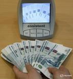 Сотрудник банка проверяет купюры в Санкт-Петербурге 4 февраля 2010 года. Рубль удерживает небольшой плюс на полуденных торгах понедельника - последнего дня уплаты налога на прибыль, потеряв поддержку нефти, развернувшейся вниз.  REUTERS/Alexander Demianchuk