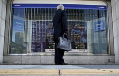 Un peatón mira un tablero electrónico que muestra los índices de mercado de varios países, afuera de una correduría en Tokio, Japón, 26 de febrero de 2016. Las bolsas de Asia cedían el lunes después de que una reunión del fin de semana del G20 terminó sin una nueva acción coordinada para impulsar el crecimiento global y luego de que datos estadounidenses sólidos reavivaron las expectativa de que la Reserva Federal elevará las tasas de interés este año. REUTERS/Yuya Shino