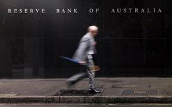 A businessman walks past the headquarters of Australia's Reserve Bank in Sydney, November 3, 2015. Australia's central bank left interest rates unchanged on Tuesday for a sixth straight month while Australian shares rose on Tuesday as bank stocks bounced back from the previous session. REUTERS/Jason Reed