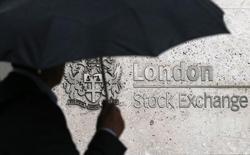 Прохожий с зонтом у здания Лондонской фондовой биржи. 24 августа 2015 года. Европейские фондовые рынки показывают положительную динамику во вторник на фоне подорожания бумаг London Stock Exchange после слухов о возможном контрпредложении Intercontinental Exchange о покупке британской компании, а также благодаря слабости евро, которая поддержала автомобильный сектор. REUTERS/Suzanne Plunkett