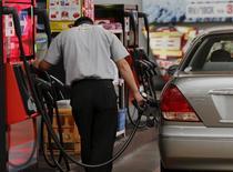 Мужчина заправляет машину в Токио 26 августа 2015 года. Азии впервые более чем за 15 лет угрожает дефицит бензина в связи с дешевой нефтью и ростом продаж автомобилей. REUTERS/Toru Hanai