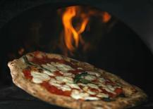 A pizza is removed from a wood-burning oven, in this file photo in Naples August 27, 2008.  REUTERS/Ciro De Luca/Agnfoto