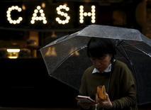 Un peatón que sostiene un paraguas y su billetera camina en un distrito comercial en Tokio, Japón. 7 de marzo de 2016. La economía de Japón se contrajo menos que lo estimado inicialmente en el cuarto trimestre del 2015, pero el consumo privado se mantuvo débil, subrayando los desafíos que enfrenta el primer ministro Shinzo Abe para restaurar el crecimiento en medio de factores desfavorables externos. REUTERS/Yuya Shino