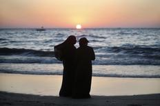 Palestinian women stand on a beach in Gaza City during sunset on summer's day August 26, 2012. REUTERS/Mohammed Salem