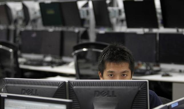 An employee of a foreign exchange trading company looks at monitors in Tokyo August 22, 2011. The dollar gained against the yen on Monday, rising from a record low plumbed late last week, as investors covered dollar short positions wary that Tokyo could step into the market and with a U.S. bank detected buying. REUTERS/Toru Hanai (JAPAN - Tags: BUSINESS) - RTR2Q6YS