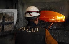Рабочий в цеху завода Русала в Красноярске. 8 июля 2014 года. Алюминиевый гигант Русал планирует рефинансировать часть предстоящих в 2016 году платежей банкам, которые оценивает в общей сложности в $1 миллиард, надеясь привлечь новые кредиты. REUTERS/Ilya Naymushin