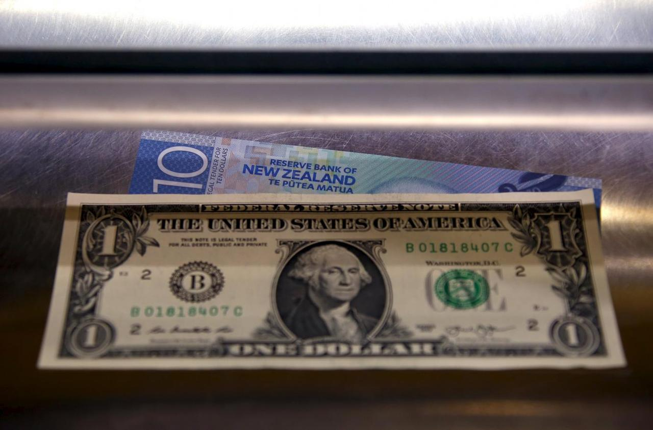 A New Zealand Ten Dollar Note Sits Underneath United States One Bill In The Window Of Currency Exchange Teller Sydney Australia March 10