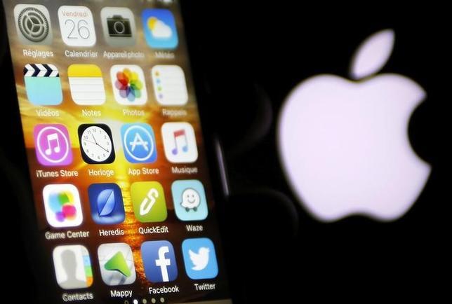 3月10日、アップルが21日にイベントを開催すると発表した。写真はiPhoneと同社のロゴマーク。フランス南西部で2月撮影(2016年 ロイター/Regis Duvignau)