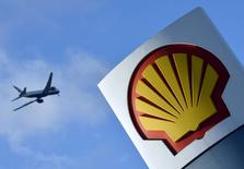 A passenger plane flies over a Shell logo at a petrol station in west London, in this January 29, 2015 file photo. REUTERS/Toby Melville/Files