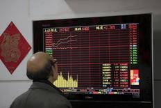 Инвестор смотрит на экран, демонстрирующий информацию об акциях, в брокерской компании в Шанхае. Акции Китая резко выросли в понедельник благодаря бумагам мелких компаний и заверениям регулятора о том, что отказываться от фондов срочной помощи преждевременно, а также комментариям, рассеявшим страхи о волне IPO. REUTERS/Aly Song