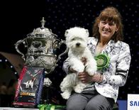 Handler Marie Burns poses with Devon, the West Highland white terrier, after winning Best in Show on the final day of the Crufts Dog Show in Birmingham, Britain March 13, 2016. REUTERS/Eddie Keogh