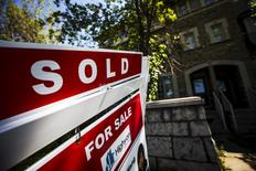 """A """"For Sale"""" sign stands in front of a home that has been sold in Toronto, Canada, June 29, 2015. REUTERS/Mark Blinch"""