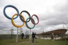 A boy takes a photograph of himself in front of the the Olympic rings in the Queen Elizabeth Olympic Park in east London April 5, 2014.   Reuters/Neil Hall
