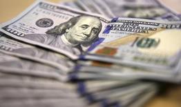 Долларовые купюры в Йоханнесбурге 13 августа 2014 года. Доллар укрепился к корзине основных валют и подрос к иене в среду, так как инвесторы настроились на новый прогноз Федрезерва относительно будущего подъёма процентной ставки. REUTERS/Siphiwe Sibeko