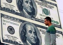 En la imagen, un hombre pasea frente a un cartel publicitario de una oficina de cambio de divisas, en cuya fachada se aprecia la imagen del dólar, en el Cairo, Egipto, el 21 de febrero de 2016. El dólar se fortalecía contra una canasta de monedas y subía contra el yen el miércoles, cuando los inversores se posicionaban para una nueva orientación de la Reserva Federal sobre el momento en que subirán las tasas de interés en Estados Unidos. REUTERS/Mohamed Abd El Ghany