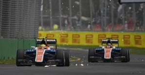 Formula One -  Australia Grand Prix - Melbourne, Australia - 18/03/16 - Manor Racing F1 driver Rio Haryanto throws up sparks in front of team mate Pascal Wehrlein during the first practice session at the Australian Formula One Grand Prix in Melbourne.   REUTERS/Jason Reed