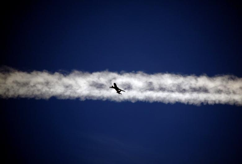 An aeroplane flies underneath the jet stream of another aircraft above the Italian city of Padova September 18, 2013. REUTERS/David Gray