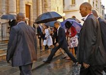 Президент США Барак Обама перешагивает через лужу во время прогулки с семьей по Старой Гаване 20 марта 2016 года. Обама в воскресенье предстал перед небольшой, но ликующей группкой кубинцев в начале исторического визита, открывшего новую главу в отношениях Вашингтона с коммунистическим правительством острова после десятилетий вражды, порождения холодной войны. REUTERS/Carlos Barria
