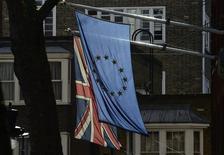 Una bandera de Gran Bretaña junto a una de la Unión Europea cuelgan de un edificio en el centro de Londres, 18 de febrero de 2016. Una votación en Gran Bretaña a favor de salir de la Unión Europea podría costarle a su economía 100.000 millones de libras esterlinas (145.000 millones de dólares) y 950.000 empleos para 2020, según un estudio encargado por la agrupación de empleadores Confederación de la Industria Británica (CBI, por su sigla original). REUTERS/Toby Melville