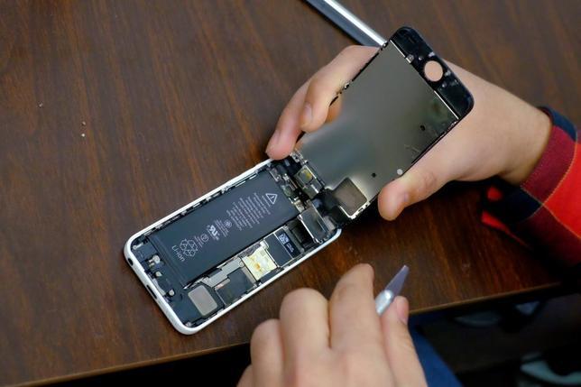 A man tries to repair an iPhone in a repair store in New York, February 17, 2016. REUTERS/Eduardo Munoz