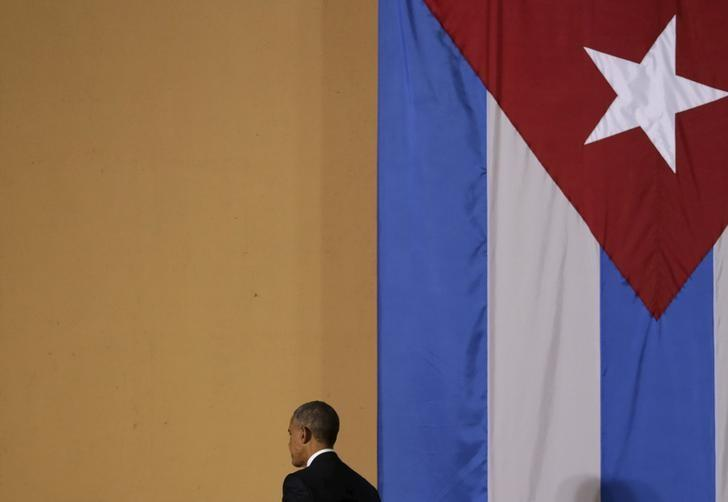U.S. President Barack Obama walks past a Cuban flag after attending a meeting with entrepreneurs as part of his three-day visit to Cuba, in Havana March 21, 2016. REUTERS/Ivan Alvarado