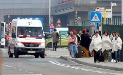 Люди после взрывов в аэропорту Брюсселя. 22 марта 2016 года. Как минимум 14 человек погибли в аэропорту Брюсселя во вторник после того, как смертник привел в действие взрывное устройство; еще 20 человек погибли вскоре при взрыве в столичном метро в час пик, сообщили массмедиа, власти и очевидцы. REUTERS/Francois Lenoir