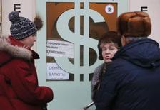 Люди у пункта обмена валюты в Москве 17 декабря 2014 года. Рубль пытается за счет продаж экспортной выручки уйти в плюс после негативного биржевого открытия среды как реакции на текущую отрицательную динамику нефти, при этом локальный спрос на рублевую ликвидность под уплату основных налогов останется, помимо колебаний нефти, основным фактором влияния в ближайшие дни. REUTERS/Maxim Zmeyev