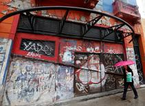 A pedestrians walks past a closed store in Buenos Aires, September 5, 2014.      REUTERS/Enrique Marcarian