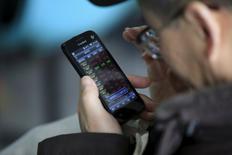 Инвестор смотрит котировки на телефоне в брокерской конторе в Шанхае. 7 марта 2016 года. Основные индексы фондового рынка Китая выросли в пятницу, завершив неделю незначительным подъемом, поскольку рыночное ралли, во время которого рынок прибавил 10 процентов за месяц, теряет темпы. REUTERS/Aly Song