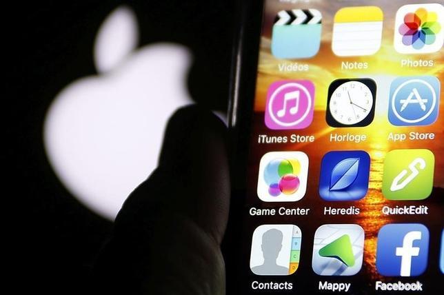 3月5日、オバマ政権内で、IT企業が法執行機関向けの「バックドア(裏口)」を自社製品に仕込むよう要請することを支持するべきか否か、意見が割れている。写真はアップルのロゴとiPhone。仏ボルドーで2月撮影(2016年 ロイター/Regis Duvignau)
