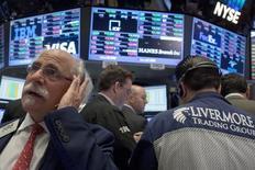 Трейдеры работают на фондовой бирже Нью-Йорка. Мартовский отчет о занятости в США и ряд других важных экономических данных, публикация которых ожидается на предстоящей неделе, возможно, помогут американским фондовым индексам возобновить свой недавний рост. REUTERS/Brendan McDermid