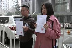 Fake marriage participants Sun Xiangshu and Shi Ci pose with divorce papers outside a court in Beijing, China, in this still image taken from video shot on March 16, 2016. REUTERS/Reuters TV
