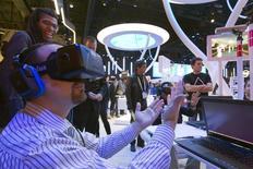 Посетитель выставки Consumer Electronics Show (CES)  в очках виртуальной реальности Oculus Rift играет в виртуальный волейбол. Лас-Вегас, 6 января 2015 года. Компания Oculus начала на этой неделе поставку долгожданных очков виртуальной реальности Rift, примерно через два года после слияния с интернет-гигантом Facebook. REUTERS/Steve Marcus