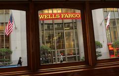 A Wells Fargo Bank sign is seen through a motorized cable car in San Francisco, California October 10, 2013. REUTERS/Robert Galbraith