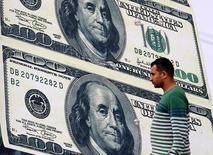 Человек идет мимо пункта обмена валют, на котором изображены долларовые банкноты. Доллар взял некоторую передышку в ходе торгов пятницы после резкого квартального падения к основным мировым валютам, поскольку участники рынка находятся в ожидании публикации данных о занятости в США, чтобы спрогнозировать дальнейшие действия ФРС в отношении повышения ключевой ставки. REUTERS/Mohamed Abd El Ghany