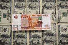 Купюра в 5000 рублей на фоне долларовых банкнот. Рубль упал в пятницу вслед за нефтью, корректируясь также и перед выходными днями после движения накануне к пикам 4 месяцев, при этом трудовая статистика США оказала умеренное влияние на котировки, существенно не выскочив за рамки прогнозов. REUTERS/Dado Ruvic