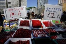 A vegetable vendor waiting for customers is seen behind price tags on fruit stall at a market in Beijing, China, March 10, 2016. REUTERS/Kim Kyung-Hoon