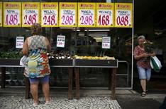 A woman looks on prices at a food market in Rio de Janeiro, Brazil, January 21, 2016. Brazil's real currency slipped to near its weakest ever against the U.S. dollar on Thursday as investors worried that erratic policy signals from President Dilma Rousseff may prolong a crippling recession in Latin America' biggest economy. REUTERS/Pilar Olivares - RTX23FYK