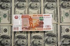 Рублевая и долларовые купюры в Сараево 9 марта 2015 года. Рубль достиг максимального с начала месяца значения в паре с долларом утром понедельника, отражая резкий рост нефти и слабость валюты США на мировых рынках, но далее ушел в минус на фоне текущего разворота нефтяных цен вниз с локальных пиков. REUTERS/Dado Ruvic