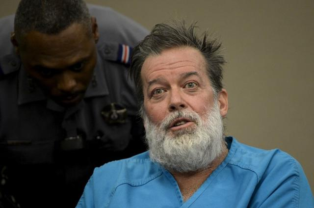 A deputy tries to calm Robert Lewis Dear, 57, accused of shooting three people to death and wounding nine others at a Planned Parenthood clinic in Colorado last month, as he spoke out at his hearing to face 179 counts of various criminal charges at an El Paso County court in Colorado Springs, Colorado December 9, 2015. REUTERS/Andy Cross/Pool