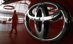 A visitor is reflected on a Toyota vehicle at the company's showroom in Tokyo in this file photo taken on June 17, 2011. REUTERS/Toru Hanai